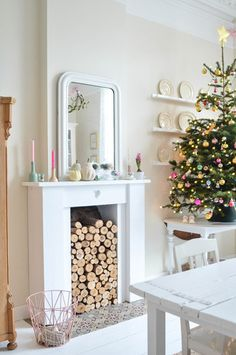 Holiday/Christmas mantel - white punctuated with pops of colour, logs in the fireplace instead of a fire