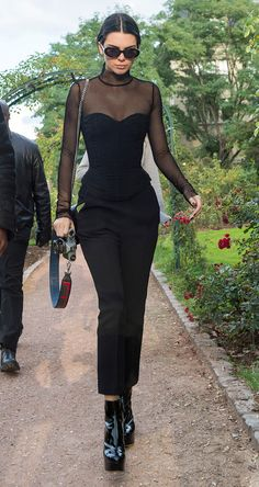 Kendall Jenner revealing how to wear a corset RN: over a sheer fishnet body stocking, black tailored trousers, patent ankle boots and retro oval sunglasses