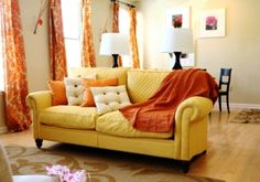 Analogous    While still warm, since dominated by yellow this room has a bright appearance but is toned down by the neutral beige walls. A feeling of formality is created in the living space from the floor-to-ceiling curtains and curved sofa arms.