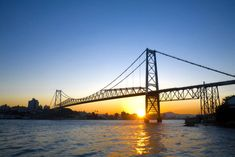 Photo about The Hercilio Luz Bridge in Florianopolis - Santa Catarina - Brazil - at sunset. Image of florianopolis, blue, reflection - 9786099 Santa Catarina Brazil, Visit Brazil, Brazil Brazil, Whatsapp Marketing, Major Airlines, Golden Gate Bridge, Places To Travel, Surfing, Around The Worlds