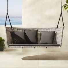 Shop Grove Outdoor Loveseat Swing.   Mermelada Estudio takes the traditional loveseat to new heights.  Hanging by two thick black ropes, handwoven faux rattan wraps round a lightweight aluminum frame to create this cozy place to lounge.