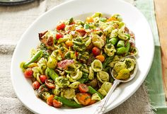 A fresh pasta salad with pork, tomato and asparagus pieces tossed in a salsa verde