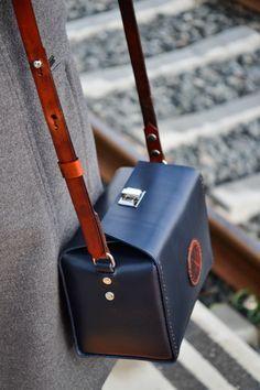 Bolso de cuero hecho a mano con un original diseño de líneas marcadas y detalles en contraste.