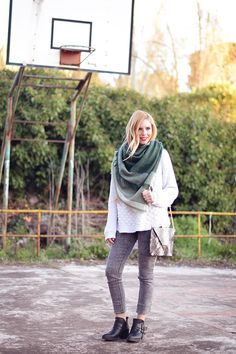 Ella está unsando la bufanda verde, el suéter blanco, los jeans gris, y las botas negro. Me gusta está equipar porque es muy bonita y linda.