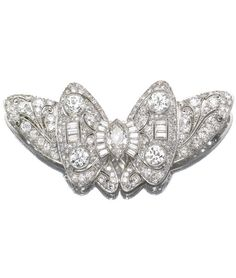 DIAMOND BROOCH, CIRCA 1935 Designed as a stylised butterfly, millegrain-set with baguette, marquise shaped, single- and circular-cut diamonds.