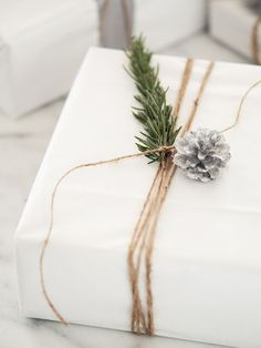 Minimal Xmas gift wrapping inspiration. Garden thread, greenery and pine cone on white paper.