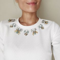 Embellished jewels white top Hand embellished top with embossed pattern fabric . Comes with extra set of bejeweled. Zip on the back for great clean cut fitting. No extra accessories needed;)) it's like a top with statement necklace.100%poly blend Tops Blouses