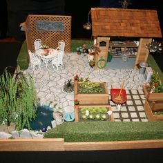 Collections of All Types From the Miniaturists of the Miniature Club of B.C.: Precisely laid out garden and shed in a dollhouse scale display by Marianne Robinson.