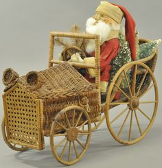 "Composition Santa with red coat trimmed in white, well detailed face with rabbit fur beard, wears long flowing stocking cap, hands at the wheel, driving one the finest looking wicker automobiles ever made, the back compartment is loaded with bottle brush trees, motor cover opens for candy or toy storage. 20"" l. (VG - Exc. Cond.)"