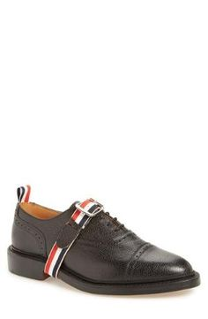 A classic cap-toe oxford crafted in rich pebbled leather is elevated by logo straps encircling the instep and accenting the heel. Color(s): black leather. Brand: THOM BROWNE. Style Name: Thom Browne Cap Toe Oxford With Logo Strap (Men). Style $1290.00