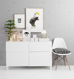 Inspiration till tavelväggar och tavelcollage i barnrum. Barntavlor ovanför byrå. Snygg vit inredning. Prickig tapet, guldprickar. Desenio.com