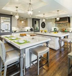 Two kitchen islands create generous traffic corridors and distinct zones: one near the range for prep and another where the family can gather. Touches such as antiqued mirrored panels with decorative grillework for separate freezer and refrigerator columns upped the style.  | Flooring: @hardwoodforless | Countertops: pentalgm | Range: Wolf | Cabinetry: @signature1981 | Refrigerator and freezer: Sub-Zero | Custom Vent hood: @AmoreDF | Sinks, faucets, pot filler: @rohlfaucets | Island Pendants: @hudsonvalleylgt
