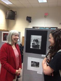 Ames High School art teacher Sandy Quintero, left, and sophomore Amy Staebler flank Staebler's photo at the CIML Art Show.