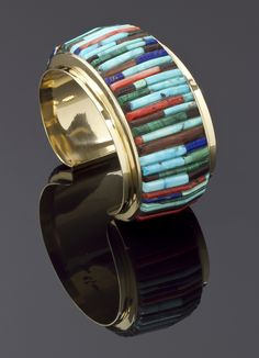 Charles Loloma, 14k gold bracelet has corn row inlay of Kingman turquoise, Mediterranean coral, ironwood, lapis and malachite.  Measures 5 1/2″ with a 1 1/8″ opening.  1 1/2″ width.