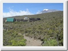 """From """"Kilimanjaro: One Man's Quest to Go Over the Hill"""" On Sale Now - Horombo Huts with Mt. Kilimanjaro (Kibo Peak) in the background - worldadventurers.wordpress.com"""