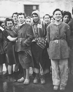 A group of female survivors stands outside a barracks in the newly liberated Lenzing concentration camp. Lenzing, a sub-camp of the Mauthausen concentration camp, was established in the fall of 1944 near the town of Vocklabruck, Austria, to provide workers for a local paper factory. It held approximately 500 forced laborers, all women. In January 1945 almost 100 female prisoners arrived at Lenzing from the recently evacuated Auschwitz concentration camp.