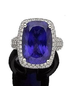 A tanzanite and diamond ring The raised oval mixed-cut tanzanite, within a surround and shoulders pavé-set with brilliant-cut diamonds, to an 18 carat white gold band, diamonds approx. 1.75cts total, maker's mark 'JC', partial London hallmark, European convention mark, ring size M