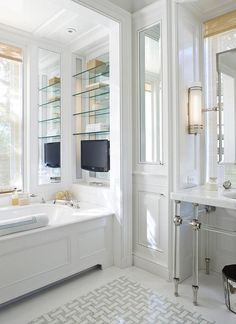 Chic master bathroom boasts a nickel and glass 6 leg washstand under a rectangular pivot mirror placed in front of a mirror dressed in a light bamboo roman shade.