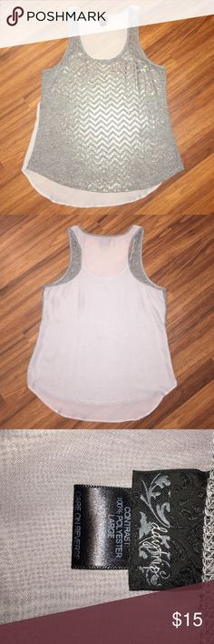 Daytrip Silver Sheer Back Tank from Buckle Daytrip Silver Sheer Back Tank from Buckle. Silver and Grey in front with chevron lines. Front is not Sheer. Back is Grey and is Sheer. This is a super cute piece to layer with! Great condition. Buckle Tops Tank Tops