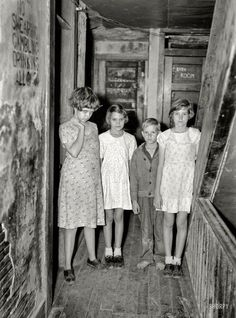 "ANUARY 1937. ""CHILDREN OF CITRUS WORKERS IN HALLWAY OF APARTMENT HOUSE. WINTER HAVEN, FLA."""