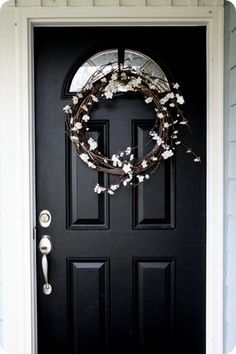 Pussy willow or blossoms make beautiful wreaths against a black door.