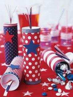 """Favors for the Fourth -- Start with mailing tubes that have plastic lids. Cut red, white, and blue paper and ribbon to size; apply them to tubes using Perfect Glue 1. Trim each tube with a star cutout. Poke a slit in the lids and insert paper """"fuses"""" into each hole. Fill with candy or pop-its."""