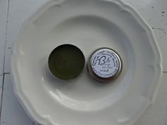 """Wildcrafted Healing Salve.   Plants known to reduce inflammation by cooling irritated skin are made into a salve.  They will relieve any skin wound such as rashes or blisters, bites or scrapes, itches or irritations.  I collected and infused these tiny miracles.   Contains Sunflower oil, violet, plantain, tea tree oil, lavender oil,  rosemary oil and vitamin E.   Packaged in a reusable 2"""" diameter tin."""