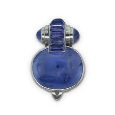 ENE BOIVIN. A PLATINUM, WHITE GOLD AND SAPPHIRE CLIP. Of geometric design, centring on a large collet-set cabochon sapphire to a tubular surmount wrapped in a line of channel-set angular sugar-loaf sapphires, to cabochon sapphire terminals, 1933. French assay marks, french maker's marks, weight 26g.