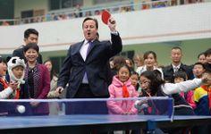 El primer ministro británico, David Cameron, juega a tenis de mesa con estudiantes de una escuela de primaria durante su viaje a Chengdu, pr...