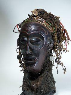 Lwena Mwana Pwevo Mask. Angola. 24 cm. Wood, beads, buttons, coins, cloth, skin, raffia. 2nd half 20th C. Collection PD-Jipsinghuizen-NL