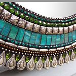 Teal Drop by Angie Heinrich. A shimmering mosaic of Italian glass tiles, faceted beads, and patterned metal surrounds this mirror with color and light. Using traditional mosaic techniques, the artist arranges hundreds of tiny pieces on a sturdy birch base, then finishes it with colored cement to create a stunning jewel for your wall. Can be hung vertically or horizontally. Hanging hardware included.