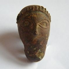 Human head mount. Hairstyle/headdress represented, with lentoid eyes but no mouth. It is possibly a sword pommel though bucket handle mount is feasible. Difficult to work out which though.