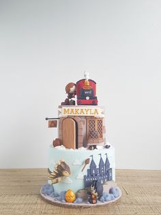 harry potter themed cake, two tier cake, portraying hogwarts and hut, hogwarts express and hermione on top Harry Potter Torte, Harry Potter Wedding Cakes, Harry Potter Birthday Cake, Harry Potter Hermione Granger, Ron Weasley, Happee Birthdae Harry, Hogwarts, Monster Book Of Monsters, Cakes For Boys