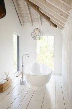 2e verdieping: Mooie combinatie van een witte houten vloer met houten balken en een groot wit losstaand bad