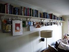 Materials: Ekby Valter brackets, Dignitet curtain rail system    Description: Spanning about 5m, this is a practical book shelf at head height with an integrated rail for clipping photos, postcards or basically any signiciant tosh lying around your flat.