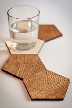 Set of 6 pentagon shaped coasters. The coasters are in 1/4 plywood, one side is etched with a geometric pattern and stained and the other with a