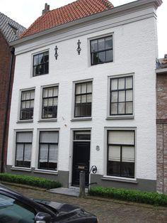 Bij deze witte gevel, RAL 9016 komen de donkere kozijnen en voordeur goed tot zijn recht. www.biggelaarverfenwand.nl
