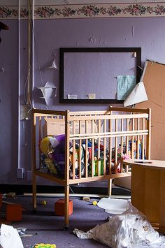Crib full of toys and books at an abandoned State Hospital (Brookside?)   ---   (by AeroFennec, via Flickr)