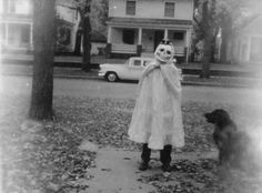 A child is ready to trick or treat as their dog watches in this vintage photo.