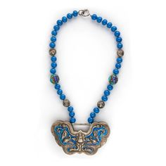 An antique or vintage sterling silver large Chinese lock with blue enamel and a repoussé bat is the focus of this newly assembled necklace.  The lock is most likely post-Qing dynasty made in the Republic period (1912-1949}.  This lock is not an export piece; it was purchased by a collector traveling in China 10 years ago and used by a Chinese family.  The lock is strung  with early 20th century opaque blue Chinese beads,  coin silver beads and enamel beads.    Finished with a silver snap…