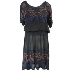 1920's beaded drop waisted dress. Snaps shut up the side and along the sleeve. Scalloped Sleeves. Lined with a silk slip.