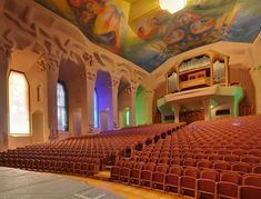 Goetheanum - Grosser Saal / Great Hall. Performance hall showing carved columns, stained-glass windows and painted ceiling.