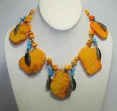 "Big Orange Howlite slabs measure up to 56mm! The slabs are separated by Turquoise nuggets and brass leaves. A brass chain completes the necklace that can be worn from 16"" up to 19"""