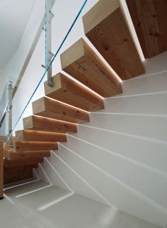 Solid chunky floating steps against a white wall with glass balustrade and steel handrail