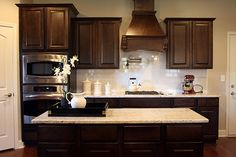 Dark cabinets, white subway tile backsplash, and Revere Pewter walls.