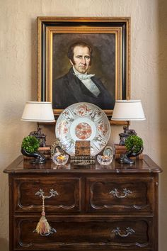 A perfectly balanced arrangement of antiques adorns this French country chest. In addition to the antique portrait -- which makes a strong impact -- antique art items include bronze Blackamoor hands holding boxwood balls and an antique Imari charger. A tassel adds the finishing detail to the storage chest.