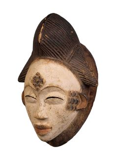 """Punu Dance Mask Okuyi Wood, kaolin, iron stand, Punu Okuyi, high 32 cm. Punu Dance Mask Okuyi, this mask has a high headdress with a central lobe flanked by long sloping side braids, finely scored. The elongated, expressively modelled face coated with whitened clay has the usual large """"scale"""" motifs dyed with red pigment. Broad incised eyebrows and eyes with curved slits."""