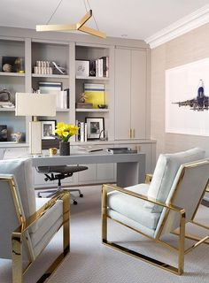 Contemporary gold and gray home office boasts two gray chairs on gold bases placed on a gray rug facing a modern gray waterfall desk.