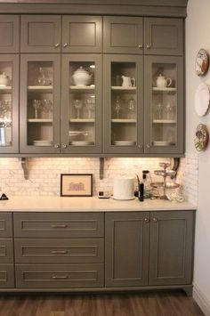 gray cabinets. Glass in first level. White counter tops, wood floor.