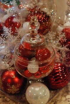 Fill a glass jar with your favorite colored ornaments & surround it by loose ornaments & snowflakes. So cute.